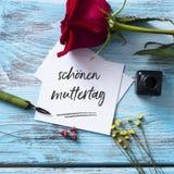 红色玫瑰和文本愉快的母亲节用德语 库存图片