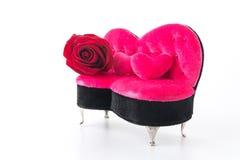 红色玫瑰和桃红色沙发 免版税库存照片