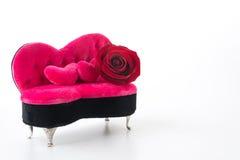 红色玫瑰和桃红色沙发 库存照片