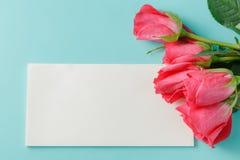 红色玫瑰和空白的礼品券文本的在纸背景 图库摄影