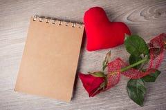 红色玫瑰和笔记本在老木背景 图库摄影