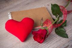 红色玫瑰和笔记本在老木背景 库存照片