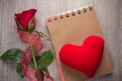 红色玫瑰和笔记本在老木背景 免版税库存图片