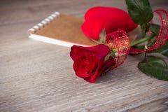 红色玫瑰和笔记本在老木背景 免版税图库摄影