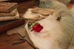 红色玫瑰和美丽的纤管在葡萄酒书桌上 库存图片