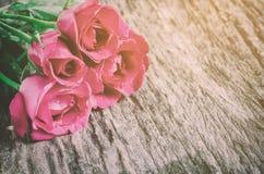 红色玫瑰在木背景的花花束与葡萄酒口气 免版税图库摄影