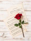 红色玫瑰花和音乐笔记板料 免版税库存照片
