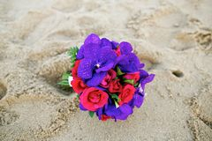 红色玫瑰花和紫色兰花婚礼花束在沙子 库存照片