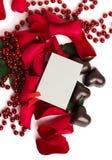 红色玫瑰花瓣和糖果在心脏的形状 免版税库存图片