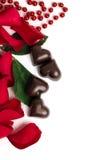 红色玫瑰花瓣和糖果在心脏的形状 库存图片