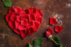 红色玫瑰花瓣在心脏在黑褐色和金黄背景塑造 爱,浪漫史,周年,华伦泰` s天概念 图库摄影