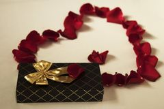 红色玫瑰花瓣心脏和礼物 免版税图库摄影