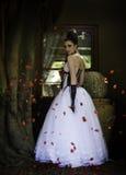 红色玫瑰花瓣围拢的幻想新娘 库存照片