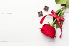 红色玫瑰,在白色木背景的巧克力 免版税库存图片