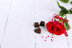 红色玫瑰,在白色木背景的巧克力 库存照片