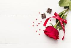 红色玫瑰,在白色木背景的巧克力 免版税库存照片