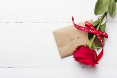 红色玫瑰,在白色木背景的爱消息 免版税图库摄影