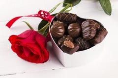 红色玫瑰,箱在白色木背景的巧克力 免版税图库摄影
