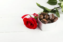 红色玫瑰,箱在白色木背景的巧克力 库存图片