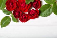 红色玫瑰 在一张白色deoevian桌上的美丽的花 免版税图库摄影