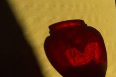 红色玻璃花瓶的阴影 免版税库存照片