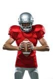 红色球衣的愤怒的拿着球的美国橄榄球运动员和盔甲 免版税库存照片