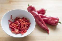 红色甜尖的胡椒和切成小方块的和平在一个白色碗在w 免版税库存照片