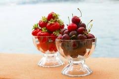 红色甜樱桃和草莓在玻璃 图库摄影
