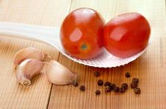 红色用了卤汁泡在白色塑料匙子,黑胡椒的蕃茄 库存照片