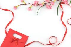 红色用假桃红色花装饰的礼物袋子和丝带 免版税图库摄影