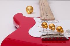 红色电吉他和圣诞节装饰 免版税库存图片