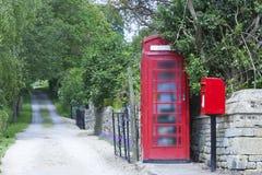 红色电话亭和邮政箱子在一条农村路 免版税库存图片