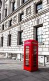 红色电话箱子在伦敦,英国,后面是大厦 库存照片