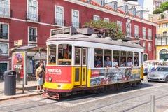 红色电车乘坐在里斯本下街道  免版税库存照片