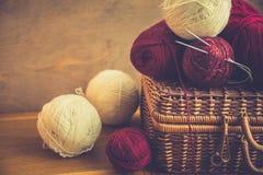 红色白色毛纱葡萄酒柳条胸口蒴线团,在木桌上的针,编织,工艺,爱好概念 免版税图库摄影