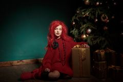 红色的一个十几岁的女孩编织了毛线衣,并且假发坐地板在圣诞树附近并且提出 时尚新年 免版税图库摄影
