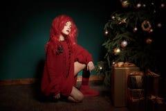 红色的一个十几岁的女孩编织了毛线衣,并且假发坐地板在圣诞树附近并且提出 时尚新年 库存图片