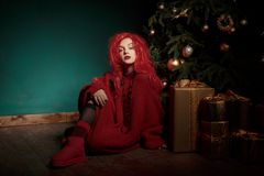 红色的一个十几岁的女孩编织了毛线衣,并且假发坐地板在圣诞树附近并且提出 时尚新年 免版税库存图片