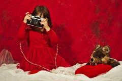 红色的一个女孩使用葡萄酒照片照相机 免版税库存图片
