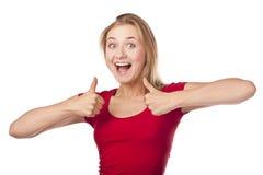 红色的可爱的女学生,翘拇指 库存照片