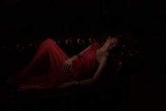 红色的夫人在一个暗室 库存图片