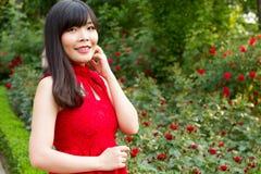 红色的女孩在玫瑰园 图库摄影