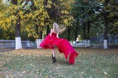 红色的女孩在秋天公园 库存图片