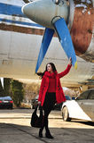 红色的女孩在老飞机背景  免版税库存照片