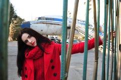 红色的女孩在老飞机背景  库存图片