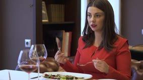 红色的妇女在餐馆和吃坐可口沙拉 股票录像