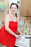 红色的妇女清洗煤气炉与三聚氰胺海绵 免版税库存照片