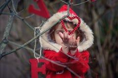 红色的小女孩与心脏装饰品 图库摄影