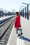 红色的少妇在火车站 库存照片