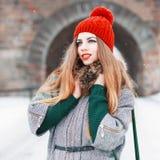 红色的年轻人相当欧洲妇女编织了帽子和时髦的winte 库存图片